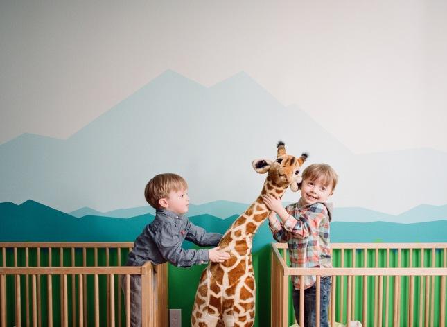 Brothers sharing stuffed animal in cribs